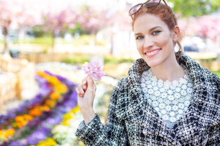 Happy young redhead Caucasian woman with toothy smile holding pink cherry blossom portrait