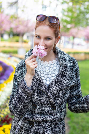 Happy young redhead woman smelling cherry blossom in park at springtime