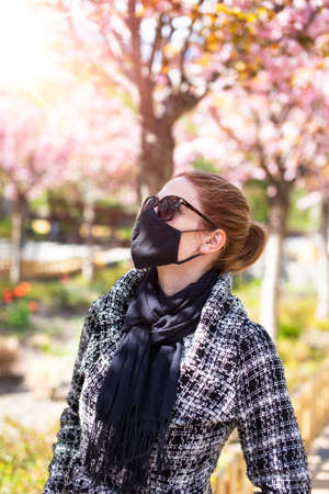 Young redhead woman in mask walking during Sakura, cherry tree blossom during day