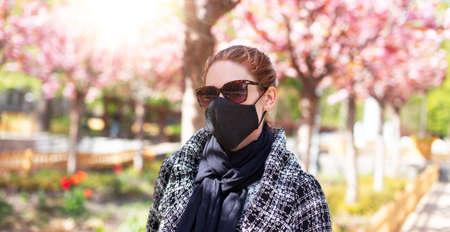 Young redhead woman in black mask at park during Sakura, covid-19