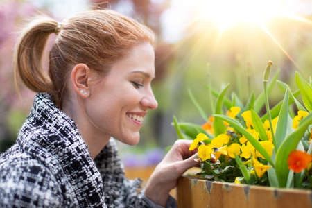 Happy young balanced Caucasian woman looking to flowers in park, profile view portrait