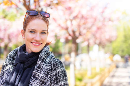 Young cheerful redhead woman in park during Sakura, empty space