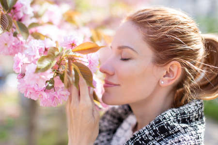 Young positive woman smelling cherry blossom, profile view, eyes closed 版權商用圖片