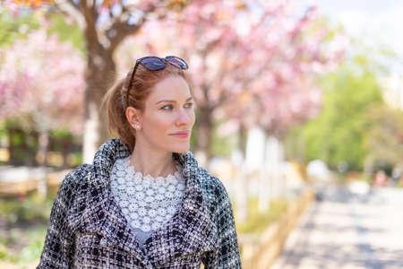 Young woman walking at park during springtime Sakura, shallow depth of field 版權商用圖片