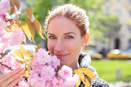 Happy young cheerful Caucasian redhead woman holding cherry tree branch