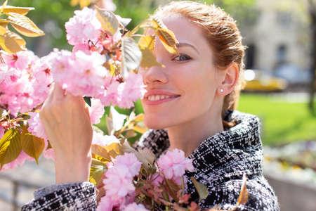 Young Caucasian positive woman hiding by cherry tree branch portrait 版權商用圖片
