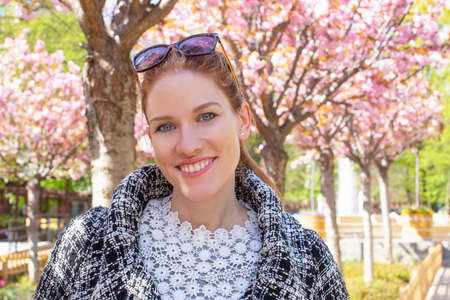 Happy young Caucasian woman in park with toothy smile during Sakura portrait, cherry blossom tree