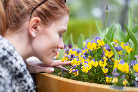 Young woman smelling yellow flowers in park during springtime portrait