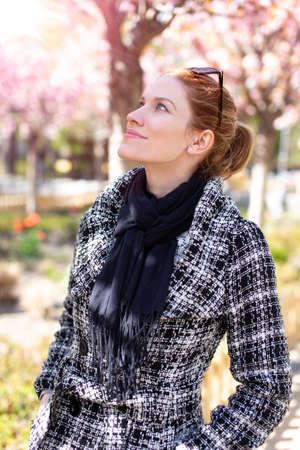 Young Caucasian cheerful redhead woman walking at park during Sakura, cherry blossom tree, looking up 版權商用圖片