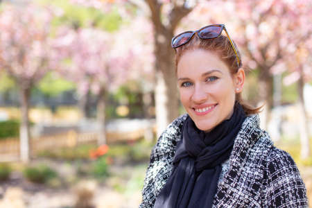 Happy young Caucasian redhead woman in park during Sakura toothy smile portrait, empty space