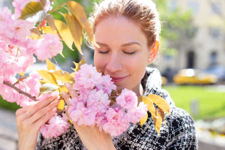 Young cheerful Caucasian redhead woman smelling cherry flower on branch