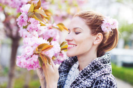 Happy young natural woman holding cherry blossom during Sakura outdoors 版權商用圖片