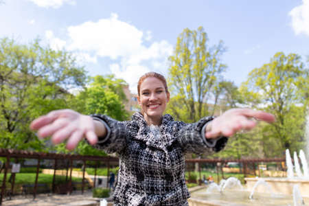 Happy young woman reach out her hands into the camera outdoors in park