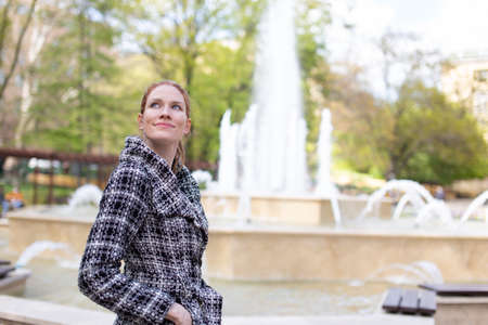 Young woman watching onto sky during walking in park at fountain, cold springtime