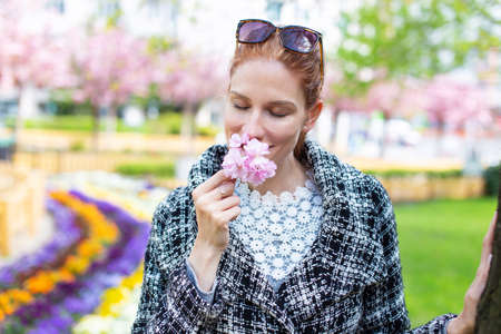 Young woman smelling cherry blossom at public park
