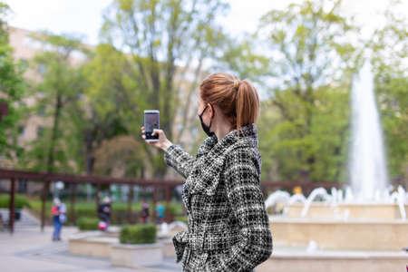 Young redhead woman taking selfie at pulic park 版權商用圖片