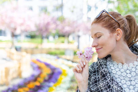 Cheerful young redhead woman smelling cherry blossom, empty space