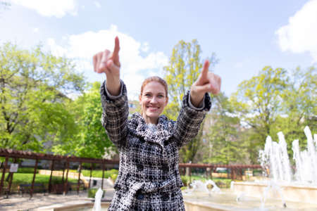 Happy young woman pointing with finger both arms in public park