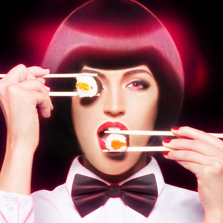 Beautiful woman eating sushi with chopsticks with pink neon lights