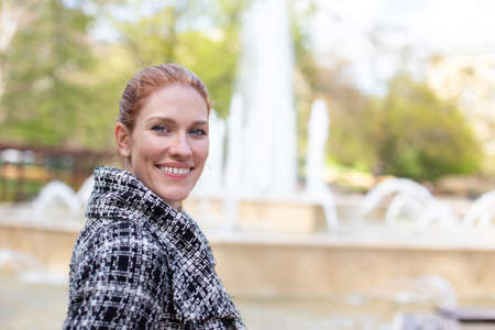 Young caucasian woman looking into camera at fountain during springtime, horizontal