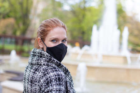 Young woman in black mask looking back at public park with fountain 版權商用圖片