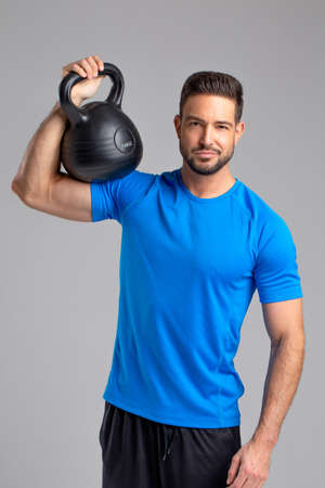 Young sporty fit 30s caucasian man posing with kettlebell on gray background