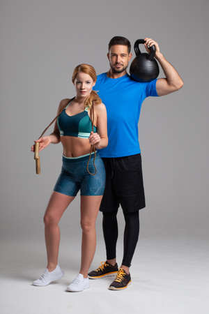 Fit Caucasian couple posing with jump rope and kettlebell in studio on gray background