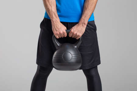 Strong man holding kettlebell on gray background