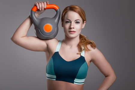 Young fit redhead Caucasian woman holding kettlebell on shoulder 版權商用圖片