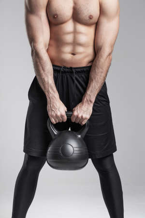 Strong muscular man body holding kettlebell on gray background