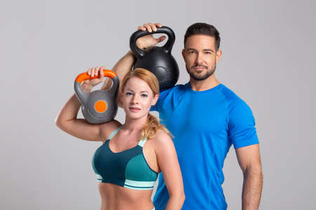 Young Caucasian fit couple holding kettlebells on shoulder 版權商用圖片