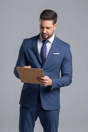 Professional businessman making notes on clipboard, gray studio background 版權商用圖片