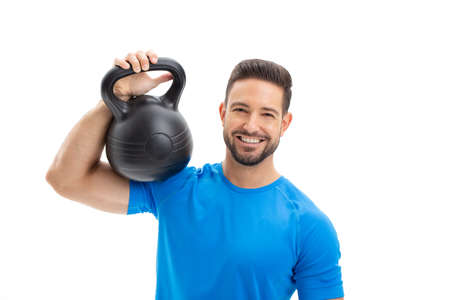 Happy young Caucasian man with toothy smile holding kettlebell on shoulder, isolated on white background
