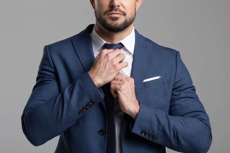 Confident professional businessman adjusting the tie concept