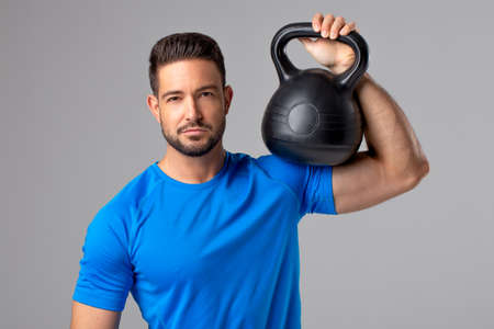 Young sporty fit 30s caucasian man in blue T-shirt posing with kettlebell on gray background