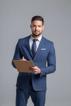 Confident young Caucasian professional manager holding checklist on gray background