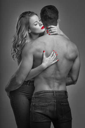 Sensual woman with red lips embracing boyfreind, black and white with red, selective coloring