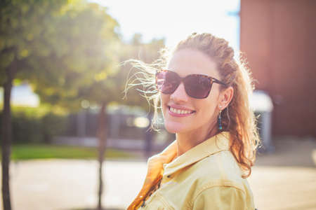 Young positive woman looking back with toothy smile at outdoors in park 版權商用圖片