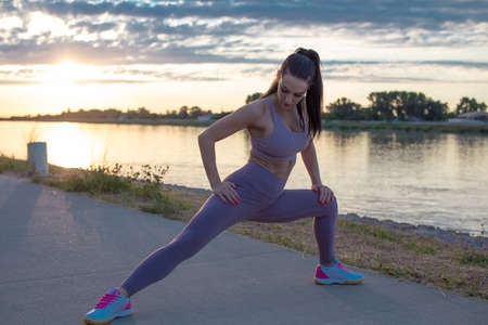 Young Caucasian woman stretching before running, warm up exercise in sunrise
