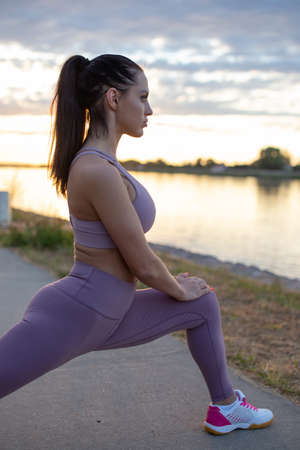 Young Caucasian woman stretching before running, warm up exercise, profile view