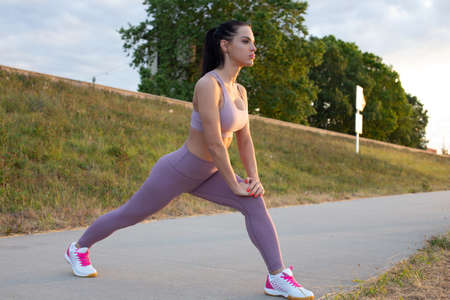 Young Caucasian woman doing lunge warm up exercise at embankment before running