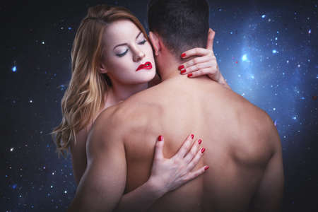 Sensual woman biting red lips while embracing boyfreind in starry night heaven