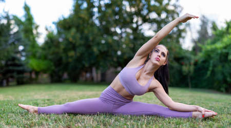 Woman doing yoga splits stretching on meadow in nature, healthy lifestyle
