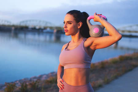Young Caucasian woman holding kettlebell on shoulder at riverside, looking away, sunset or sunrise 版權商用圖片