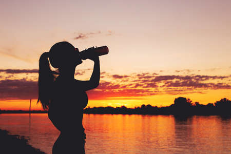 Tired thirsty woman silhouette drinking from bottle after workout in sunset 版權商用圖片