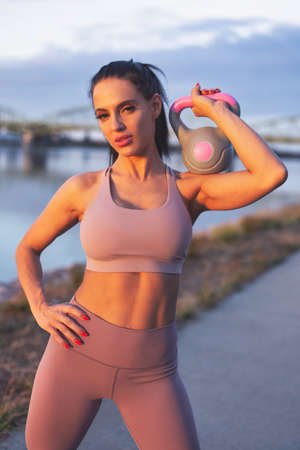 Young Caucasian woman holding kettlebell on shoulder at riverside