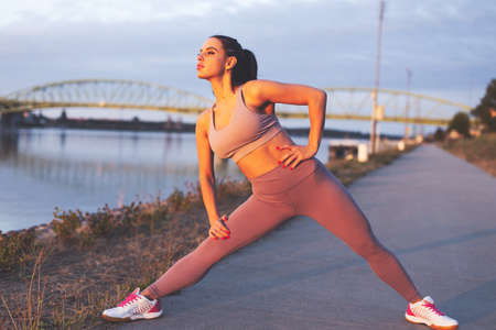 Young Caucasian jogger woman stretching legs before run at riverside