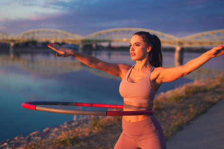 Young woman doing hoop exercise at riverside in sunset