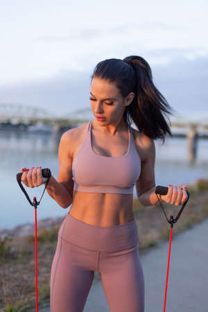 Young woman doing biceps exercise by expander at riverbank, vertical