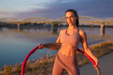 Young athlete woman holding hoop at riverbank during sunset